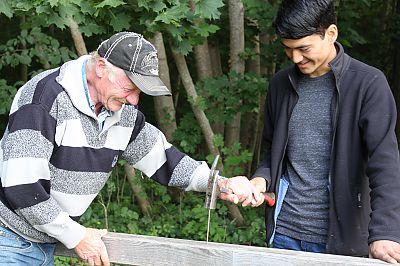 Ranger Manfred Klatt und Praktikant Mohamed Hosseini bei der Reparatur eines Fahrradständers